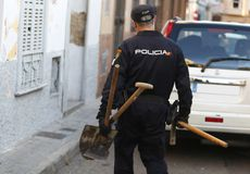 Anti drug raid in mallorca details. A police officer carry some tools during an anti drug raid in the la soledat square in palma de mallorca city stock photos