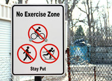 Anti Exercise Sign. Amusing white sign with No Exercise Zone and Stay Put black lettering. The funny inaction signage has generic Red and balck symbols for No Royalty Free Stock Photography