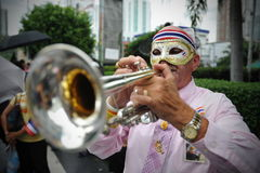 Anti-Government Protest in Bangkok. A masked protester plays a trumpet during an anti-government rally in Bangkok's shopping district on July 21, 2013 in Bangkok Royalty Free Stock Photography