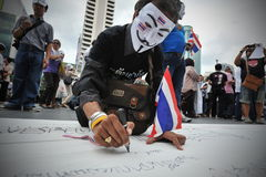 Anti-Government Protest in Bangkok. A masked protester writes anti-government slogans on a banner while participating in a rally in Bangkok's shopping district Royalty Free Stock Photography