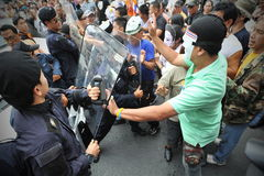Anti-Government Protest in Bangkok. Masked protesters scuffle with riot police during an anti-government rally in Bangkok's shopping district on July 21, 2013 in Royalty Free Stock Image