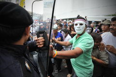 Anti-Government Protest in Bangkok. Masked protesters scuffle with riot police during an anti-government rally in Bangkok's shopping district on July 21, 2013 in Royalty Free Stock Photo