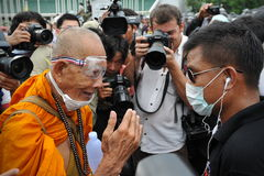 Anti-Government Rally in Bangkok. A Buddhist monk talks with a nationalist protester from the Pitak Siam group while attending a large rally on Makhawan Bridge Stock Photography