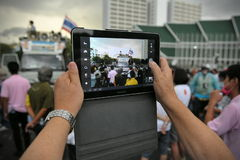 Anti-Government Rally in Bangkok. A nationalist protester from the Pitak Siam group uses a tablet computer to photograph an anti-government on Makhawan Bridge on Stock Image