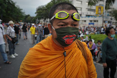 Anti-Government Rally in Bangkok. A Buddhist monk wearing a face mask attends a nationalist Pitak Siam rally on Makhawan Bridge on November 24, 2012 in Bangkok Stock Photography