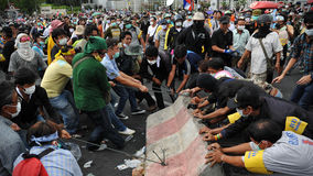 Anti-Government Rally in Bangkok. Nationalist protesters from the Pitak Siam group remove concrete barriers from a police roadblock on Makhawan Bridge during a Royalty Free Stock Image