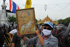 Anti-Government Rally in Bangkok. A nationalist protester from the Pitak Siam group holds up a portrait of the Thai King while taking part in a large anti Royalty Free Stock Photos