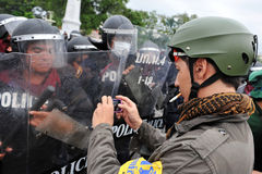 Anti-Government Rally in Bangkok. A nationalist protester from the Pitak Siam uses a mobile phone to photograph riot police while taking part in a large anti Royalty Free Stock Photography