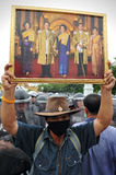 Anti-Government Rally in Bangkok. A nationalist protester from the Pitak Siam group holds up a portrait of the Thai royal family while taking part in a large Royalty Free Stock Image