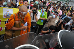 Anti-Government Rally in Bangkok. A Buddhist monk confronts riot police while attending a nationalist Pitak Siam rally on Makhawan Bridge during a large anti Stock Images