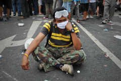 Anti-Government Rally in Bangkok. A masked nationalist protester from the Pitak Siam group sits in the road while attending a large anti-government rally on Royalty Free Stock Photo