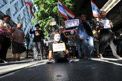 Anti-Government 'White Mask' Protest in Bangkok. A disabled protester wearing a Guy Fawkes mask leads an anti-government rally through Bangkok's shopping Royalty Free Stock Photography