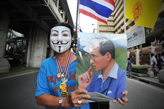 Anti-Government 'White Mask' Protest in Bangkok. An anti-government protester wearing a Guy Fawkes mask and holding a portrait of the Thai king joins a large Stock Image