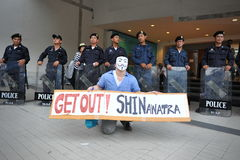 Anti-Government 'White Mask' Protest in Bangkok. A protester wearing a Guy Fawkes mask holds a sign as riot police standby at an anti-government rally in Bangkok Stock Photos