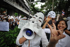 Anti-Government 'White Mask' Protest in Bangkok. Protesters wearing a Guy Fawkes masks march through Bangkok's shopping district on June 16, 2013 in Bangkok Stock Photo