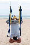 Anti--gravitation yoga, man som gör yogaövningar eller fluga-yoga på havsbakgrunden royaltyfri fotografi