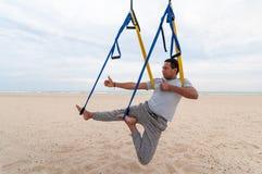 Anti--gravitation yoga, man som gör yogaövningar eller fluga-yoga på havsbakgrunden arkivfoton
