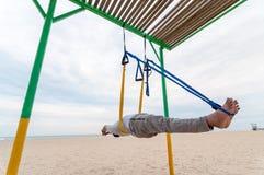 Anti--gravitation yoga, man som gör yogaövningar eller fluga-yoga på havsbakgrunden royaltyfria bilder
