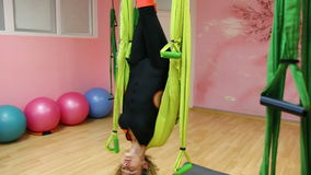Anti-gravity Yoga, athletic woman doing yoga exercises indoor stock video footage