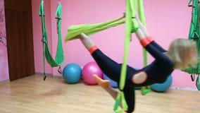 Anti-gravity Yoga, athletic woman doing yoga exercises indoor stock video