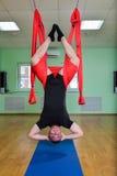Anti-gravity Yoga, mens die aerooefeningen met hangmat in klasse, bovenkant doen - neer Stock Afbeeldingen