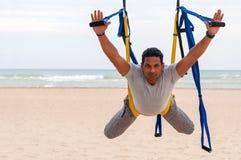 Anti-gravity Yoga, mens die yogaoefeningen op de overzeese achtergrond doen Royalty-vrije Stock Fotografie