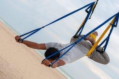 Anti-gravity Yoga, mens die yogaoefeningen op de overzeese achtergrond doen Stock Afbeelding