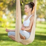 Anti-gravity Yoga outdoor. Happy woman doing yoga exercises, meditate in the park. Yoga meditation in hammock. stock photography
