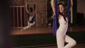 Anti-gravity Yoga, woman doing yoga exercises indoor stock video