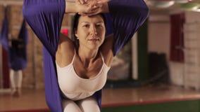 Anti-gravity Yoga, woman doing yoga exercises indoor stock video footage