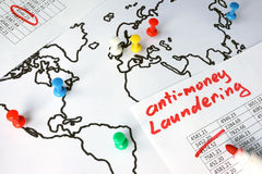 Anti-money laundering AML concept. Data and thumb tacks in a map Stock Photos