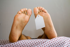 Anti natural dead feets. Dead foots with a white tag in a bed, in a non natural position Stock Photo