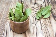 Anti-oxyderende keukenkruiden Kruiden van laurierblad in landelijke stijl Droge aromatische baaibladeren in een houten kom op wit stock afbeelding