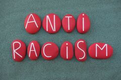 Free Anti Racism, Social Issue Slogan Text Composed With Red Colored Stone Letters Over Green Sand Stock Photos - 185208543