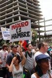 Anti--regering personer som protesterar som rymmer ett baner som läser: MADURO ÄR HUNGRIG arkivbilder