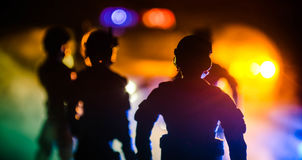 Anti-riot police give signal to be ready. Government power concept. Police in action. Smoke on a dark background with lights. Blue Royalty Free Stock Image