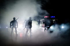 Anti-riot police give signal to be ready. Government power concept. Police in action. Smoke on a dark background with lights. Blue Stock Image