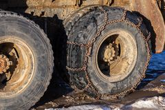Anti-skid chain on freight truck wheels at winter daylight closeup.  stock photography