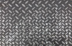 Anti slip gray metal plate with diamond pattern. Dark gray industrial anti slip embossed metal steel plate with diagonal bumps of diamond pattern texture and Royalty Free Stock Photo