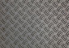 Anti slip gray metal plate with diamond pattern. Dark gray industrial anti slip embossed metal steel plate with double diagonal bumps of diamond pattern texture Royalty Free Stock Photos