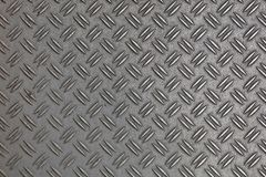 Anti slip gray metal plate with diamond pattern. Dark gray industrial anti slip embossed metal steel plate with double diagonal bumps of diamond pattern texture Stock Photography