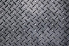 Anti slip gray metal plate with diamond pattern. Dark gray grunge industrial anti slip embossed metal steel plate with diagonal bumps of diamond pattern texture Royalty Free Stock Images