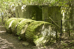 Anti tank blocks from world war 2 in woodland. A roller type anti tank block sits next to a track in woodland adjacent to a gun emplacement lookout post building Royalty Free Stock Photography