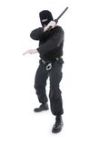 Special forces. Anti-terrorist police guy wearing black uniform and black mask holding firmly police club in one hand raised in the air ready for action, shot on Stock Photography