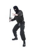 Special forces. Anti-terrorist police guy wearing black uniform and black mask holding firmly police club in one hand ready for action, shot on white Stock Photography