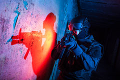 Anti-terrorist unit policeman/soldier. Special forces/anti-terrorist unit policeman or contractor during night CQB mission/operation (color toned image, blue and Royalty Free Stock Photo