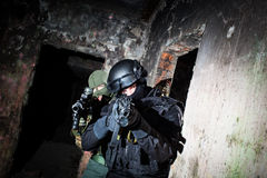 Anti-terrorist unit policeman/soldier. Special forces/anti-terrorist unit or contractor team during night CQB mission/operation (color toned image, very harsh Stock Photo