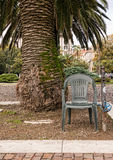 Anti theft device - chair padlocked to post. Under palm tree. Stock Images