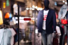 Anti theft frame at the entrance of an apparel clothes store with red security alarm indicator stock images
