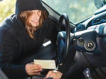 Burglar thief breaking into car stealing smartphone Stock Photos